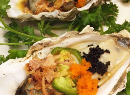 Baked oysters, tobiko caviar, garlic roasted shallot, lemon juice, Tamari-style soy sauce, and wasabi