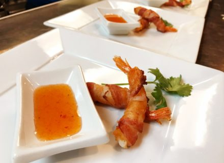 Bacon wrapped shrimp with sweet and sour sauce.