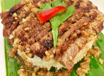 Grilled marinated tri-tip dressed with garlic-pepper sauce on a bed of jasmine rice