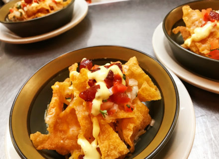 crispy wonton chips topped with savory sausage, green onion, tomato, and three different cheeses.